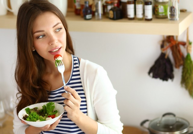 BM_Young woman eating salad and holding a mixed salad_90718075